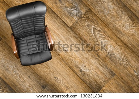 Black leather armchair on wood background. Up view
