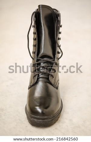 Black Leather Boot on blare cement floor    - stock photo