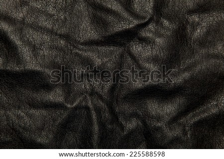 Black leather material slightly bunched so it is rippled. - stock photo
