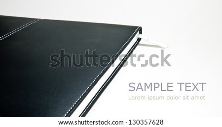 Black leather notebook, with bookmark, showing its texture isolated on white