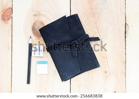 Black Leather notebooks with pencil on wood - stock photo