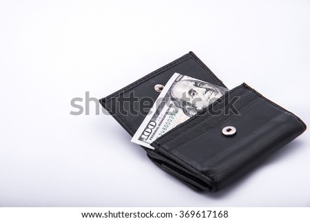 Black leather purse and one hundred dollars - stock photo
