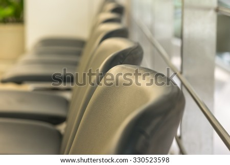 Black leather seats with glass wall in hospital - stock photo