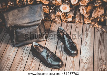 black leather shoes and a backpack on a wooden background, women's shoes