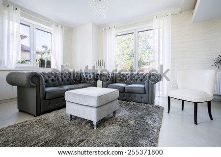 Black leather sofa in bright living room - stock photo