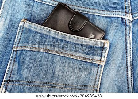 Black leather wallet sticking in the back pocket of denim  blue jeans - stock photo