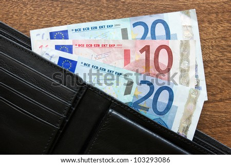 black leather wallet with euros on the table