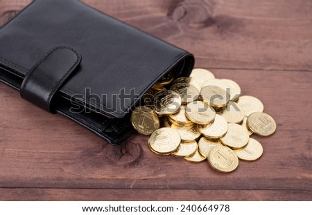 Black leather wallet with golden coins on wood background - stock photo