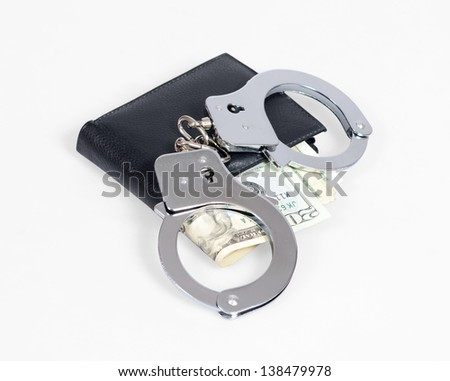 Black leather wallet with handcuffs isolated over white - stock photo
