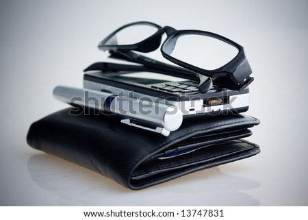 Black leather wallet with pen, mobile phone and eyeglasses - stock photo