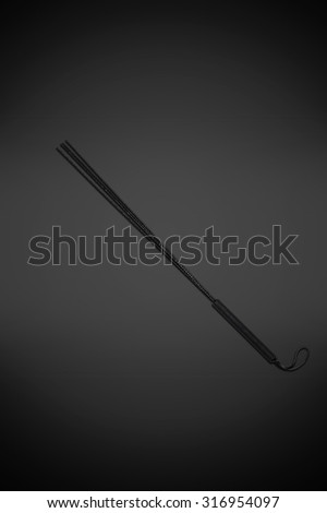 Black leather whip isolated on gray background
