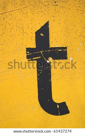 Black letter t on yellow grungy background - stock photo