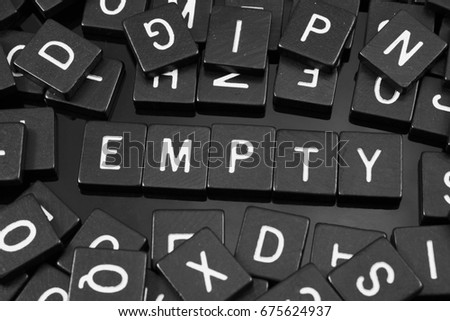 "Black letter tiles spelling the word ""empty"" on a reflective background"