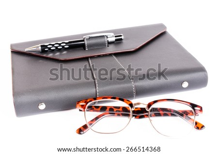 black luxury organizer and black pen with glasses isolated on white background  - stock photo