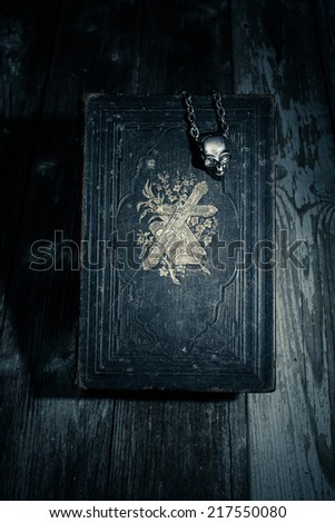 black magic on halloween bible on a wooden table with a skull chain in the night - stock photo