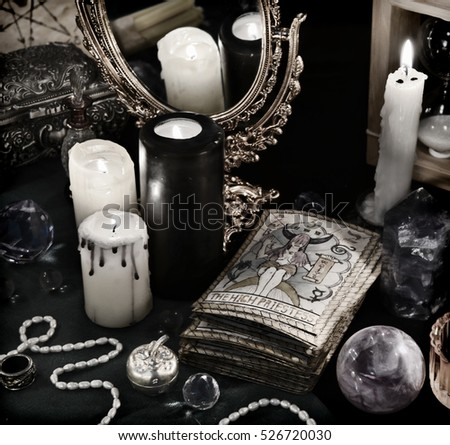 Black magic still life with the Tarot cards, mirror and burning candles in retro grunge style. Halloween concept, mystic fortune telling ritual, divination rite. Vintage objects on witch table