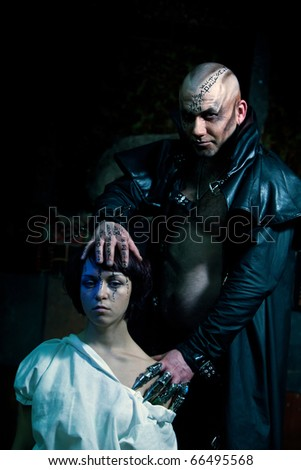 Black Magician is making ceremony with the beautiful girl. - stock photo