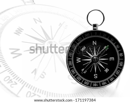 Black magnetic portable compass with a bigger transparent one on white background - stock photo