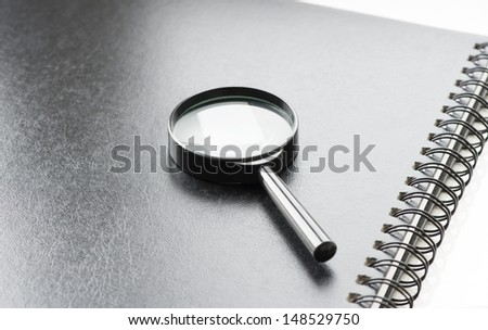 Black magnifying glass on black notebook, angle view, office background - stock photo