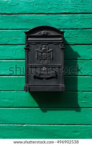 Black mail box on green wooden boards