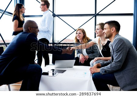 Black male executive sitting and shaking hands with white female colleague - stock photo