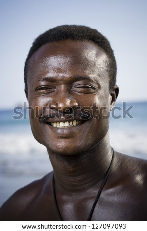 Black male posing for portrait on beach