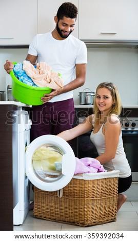 Black man and happy white girl near washing machine with linen - stock photo