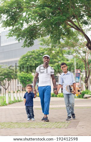 Black man and his two sons walking in the park - stock photo