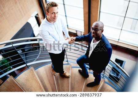Black man and white man standing on staircase facing camera smiling and shaking hands