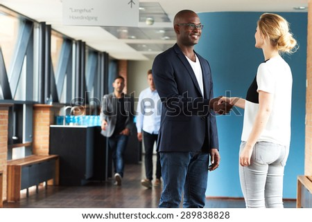 Black man and white woman smiling and shaking hands in office building - stock photo