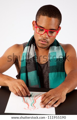 Black man drawing with a pastel, creating fashion dresses, wearing glasses and a scarf