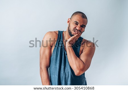 black man has a toothache - stock photo
