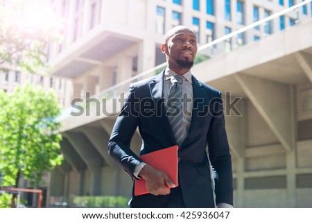 black man in a business suit standing street and uses phones and tablet computer