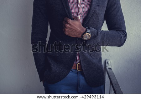 Black man in a suit with watch on wrist.