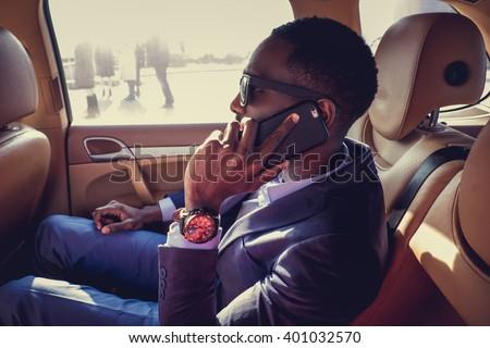 Black man in a sunglasses using smartphone in a car. - stock photo