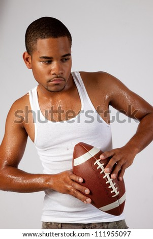 Black man in an undershirt holding an American football with sweat on his arms and chest, ready to throw the football.