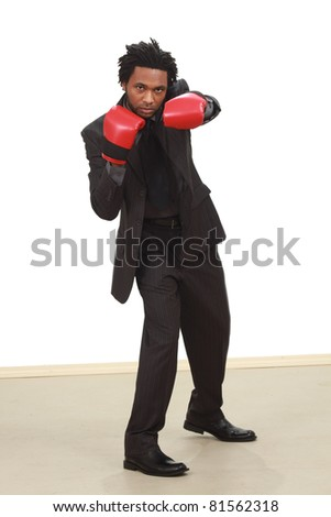Black man in business suit with boxing gloves - stock photo
