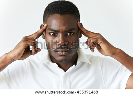 Black man in white polo shirt having bad headache. Young African American male thinking over or trying to recollect something very important, holding hands on his temples, looking at the camera.