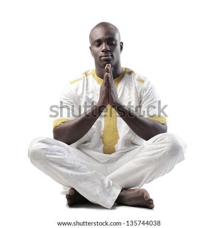 black man meditates sitting on the ground