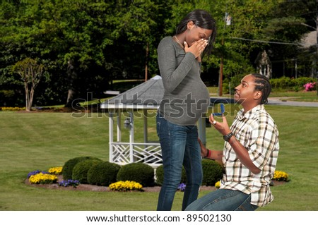 Black man proposing to a pregnant African American woman