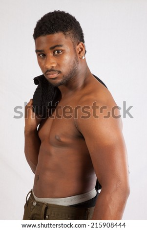 Black man shirtless   looking thoughtfully at the camera