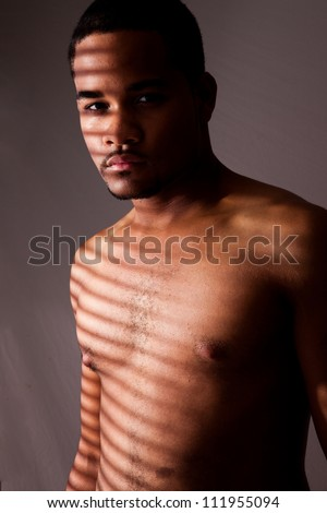 Black man standing without a shirt, showing his chest and abdomen, with light pattern from window blinds falling across his torso