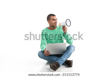 black man with laptop over white background. Young african american student seated on floor and holding loudspeaker - stock photo
