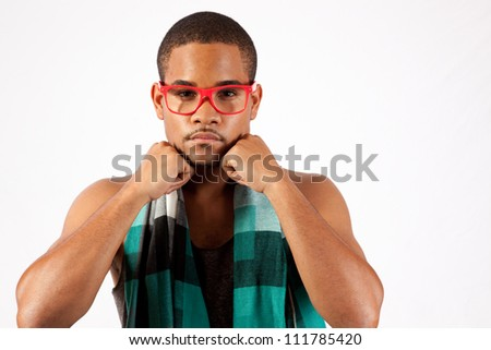 Black man with pink eye glasses with his chin resting on his fists, eye contact with the camera and a serious expression