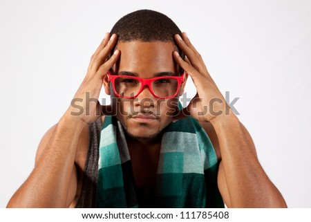 Black man with pink eye glasses with his hands up to his head, eye contact with the camera and a serious expression
