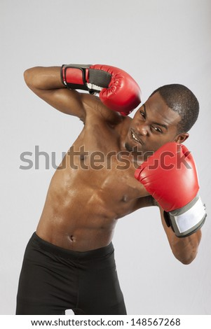 Black man with red boxing gloves, standing with gloves raided and  ready to fight, having worked up a sweat