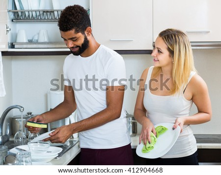 black man with smiling european white woman dusting in domestic kitchen