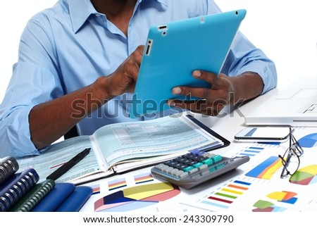 Black man working in office with tablet computer.  Accounting - stock photo