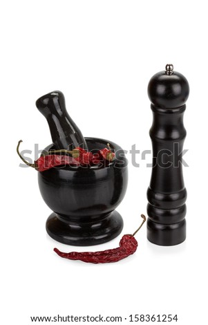 Black marble mortar and pestle with red chilli pepper isolated on white background - stock photo