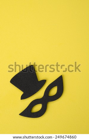 Black Mask and Hat on Yellow Foam - stock photo